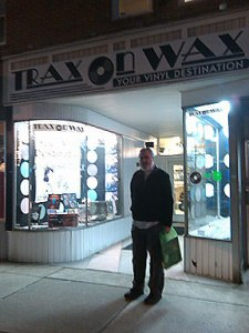 Alan Haber stands beneath the sign at Trax on Wax